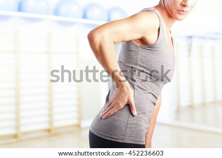 Portrait of sporty woman putting her hand on waist while has sport injury. - stock photo