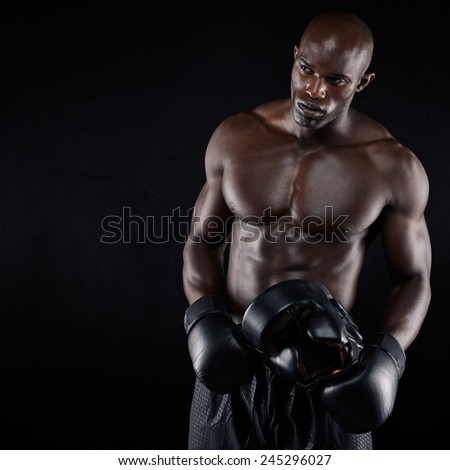 Portrait of sporty young man with muscular body holding boxing helmet. African male boxer against black background - stock photo