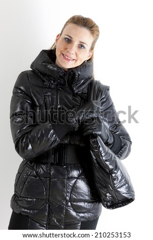 portrait of standing woman wearing black jacket with a handbag - stock photo