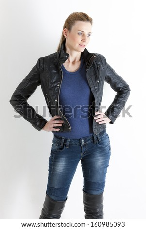 portrait of standing woman wearing jeans and black jacket - stock photo