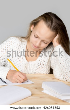 Portrait of stressed beautiful casual girl, sitting at desk, holding her head in arms with overwhelmed frustrated expression, having difficulties with hard schoolwork, studio, gray background - stock photo