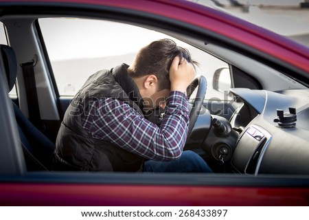 Portrait of stressed man sitting on car drivers seat - stock photo