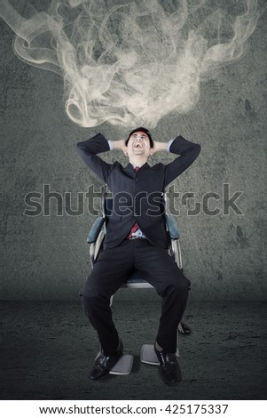 Portrait of stressful handicapped businessman sitting on the wheelchair with smoke in his head - stock photo