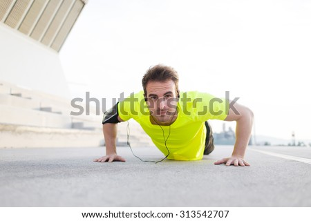 Portrait of strong build sports man doing push ups on asphalt city road and listen to music with headphones, young male jogger warm up before start his workout training outside and look to the camera - stock photo