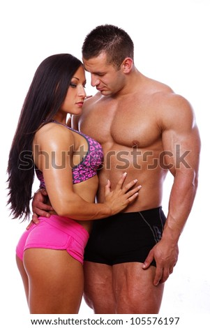 Portrait of strong couple posing in gym - stock photo