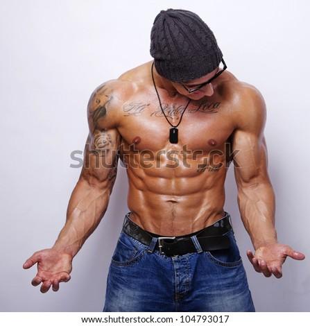 Portrait of strong man posing in studio - stock photo