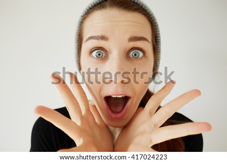 Portrait of student girl looking and screaming in surprise, mouth wide open. Young female astonished with some unexpected news or big sale prices. Human face expressions and emotions. Body language  - stock photo