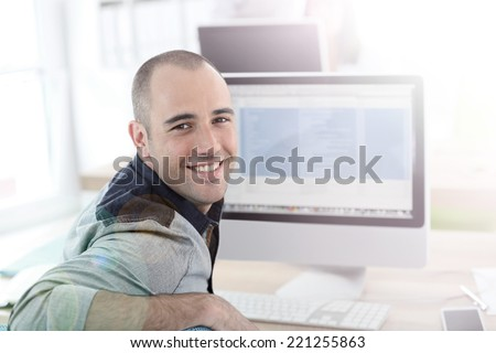 Portrait of student in front of desktop computer - stock photo