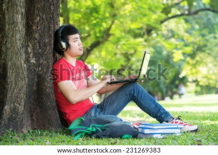Portrait of student relaxing in the park. - stock photo