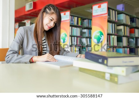 Portrait of student with open book reading it in college library ,She smile. - stock photo