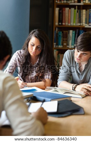 Portrait of students reviewing for the examinations in a library - stock photo
