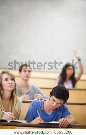 Portrait of students taking notes while their classmate is raising her hand in an amphitheater - stock photo