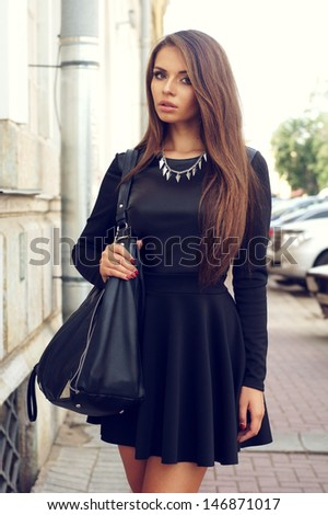 portrait of stylish beautiful girl wearing short black dress posing or walking at the street - stock photo