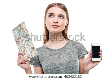 Portrait of stylish beautiful young woman isolated on white background. Woman holding map and mobile phone. Woman trying to choose between map and mobile phone - stock photo