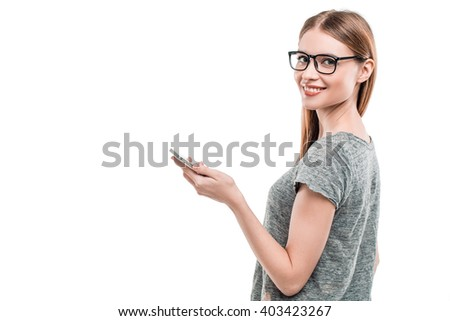 Portrait of stylish beautiful young woman isolated on white background. Woman with glasses smiling, looking at camera and using mobile phone. Free space for logo. Back view photo - stock photo