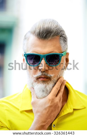 Portrait of stylish handsome adult man with beard standing outdoors. Man wearing glasses and yellow T-shirt, and looking at camera - stock photo