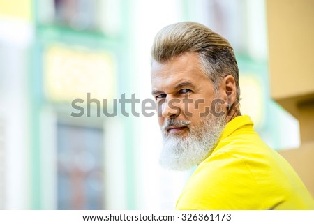 Portrait of stylish handsome adult man with beard standing outdoors. Man wearing yellow T-shirt and looking at camera - stock photo