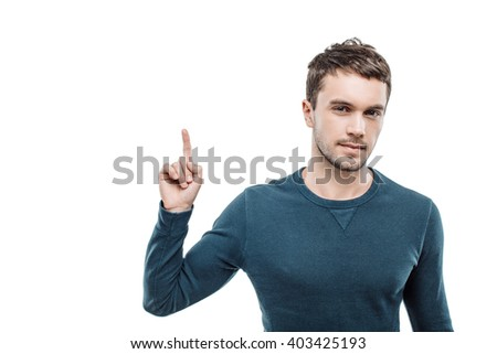 Portrait of stylish handsome young man isolated on white background. Man pointing up and looking at camera. Free space for logo - stock photo