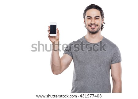 Portrait of stylish handsome young man isolated on white background. Man showing mobile phone and smiling - stock photo