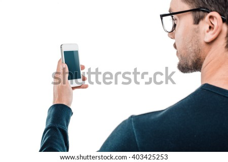 Portrait of stylish handsome young man isolated on white background. Man wearing glasses and using mobile phone. Back view photo - stock photo