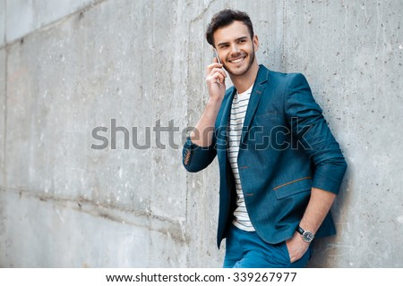 Portrait of stylish handsome young man with bristle standing outdoors and leaning on wall. Man wearing jacket and shirt. Smiling man using mobile phone - stock photo