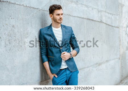 Portrait of stylish handsome young man with bristle standing outdoors and leaning on wall. Man wearing jacket and shirt - stock photo