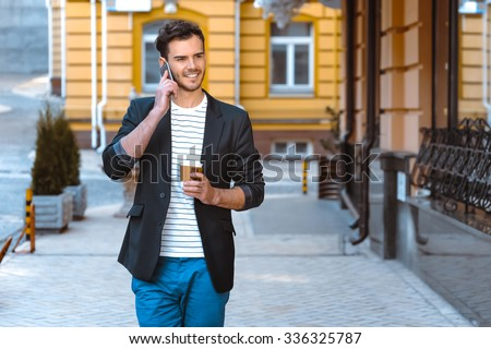 Portrait of stylish handsome young man with bristle standing outdoors. Man wearing jacket and shirt. Smiling man talking on mobile phone and holding cup of coffee - stock photo