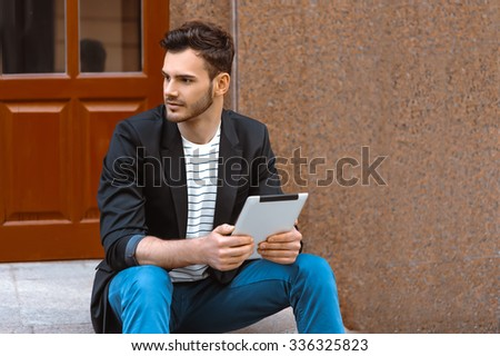 Portrait of stylish handsome young man with bristle standing outdoors. Man wearing jacket and shirt. Man using tablet computer and sitting on parapet - stock photo