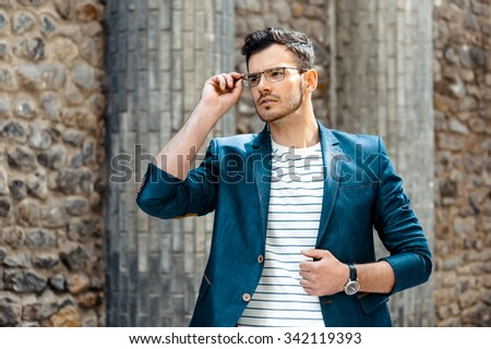 Portrait of stylish handsome young man with bristle standing outdoors. Man wearing jacket and watch. Man with glasses - stock photo