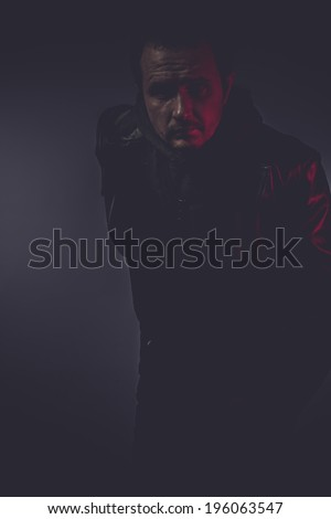 portrait of stylish man with long leather jacket, gun armed - stock photo