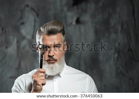 Portrait of stylish professional hairdresser with beard. Man wearing shirt, looking at camera and holding scissors near his eye - stock photo