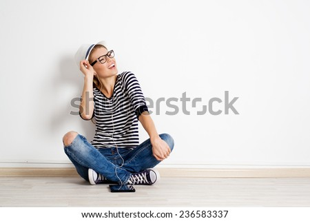 POrtrait of stylish teenage girl in hat listening songs in headphones. Happy smiling female in eyeglasses sitting on light flooring in her room. Youth and lifestyle concept.  - stock photo