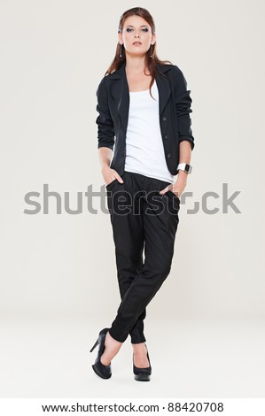 portrait of stylish woman posing against grey background - stock photo