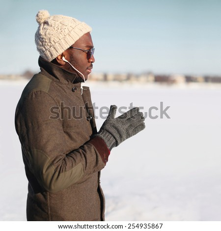 Portrait of stylish young african man listening music outdoors in winter day - stock photo