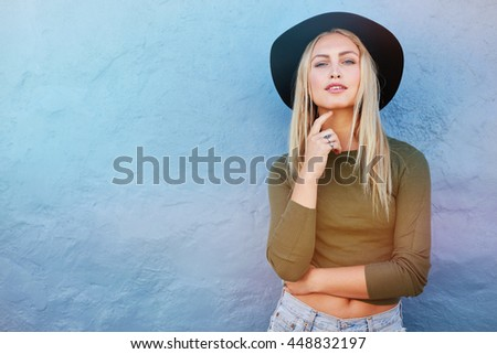 Portrait of stylish young female model looking at camera against blue wall. Caucasian young woman with copy space. - stock photo