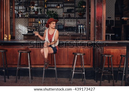 Portrait of stylish young female sitting at a cafe with drink and looking away. Beautiful caucasian female at coffee shop counter. - stock photo