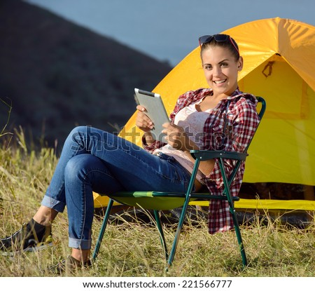 Portrait of succesful woman with tablet sitting in folding chair near camp tent outdoors - stock photo