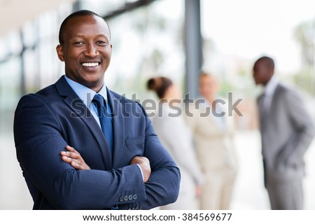 portrait of successful african office worker with arms crossed - stock photo