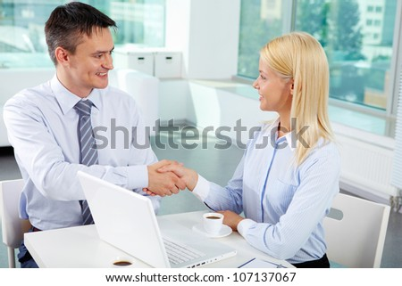 Portrait of successful associates handshaking after striking deal - stock photo