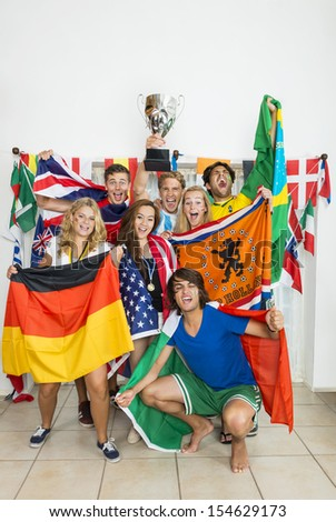 Portrait of successful athletes with various national flags celebrating at home - stock photo