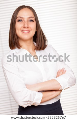 Portrait of successful brunette businesswoman with crossed hands over white isolated background - stock photo