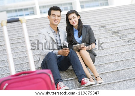 Portrait of successful business partners sitting near airport and looking at camera - stock photo
