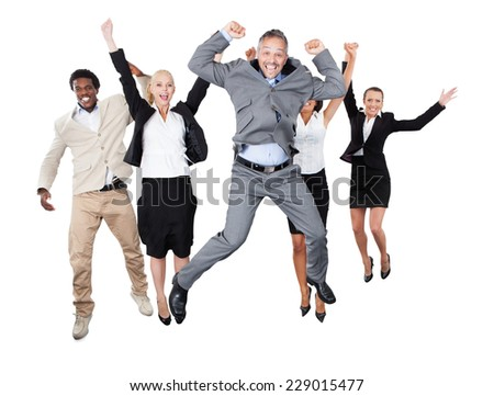 Portrait of successful business team with arms raised standing over white background - stock photo