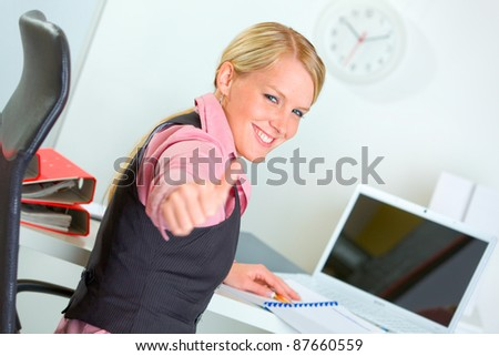 Portrait of successful business woman showing thumbs up - stock photo