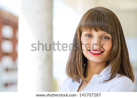 Portrait of successful business woman smiling and looking at the camera - stock photo
