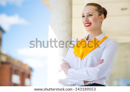 Portrait of successful business woman standing on a balcony with his arms crossed - stock photo