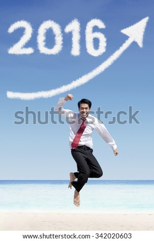 Portrait of successful businessman jumping on the beach under clouds shaped numbers 2016 and upward arrow - stock photo