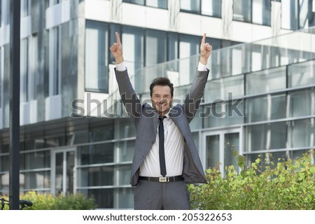 Portrait of successful businessman pointing upwards outside office - stock photo