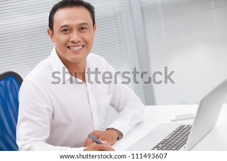 Portrait of successful businessman working at office - stock photo