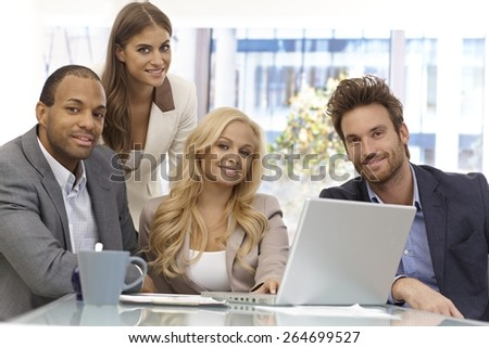 Portrait of successful businessteam sitting at table, working, smiling happy. - stock photo